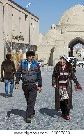 BUKHARA, UZBEKISTAN - MARCH 14, 2015:  Man and woman walk through the old town