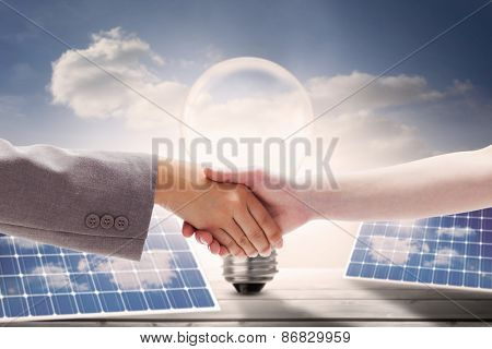 Handshake between two women against light bulb and solar panels on floorboards in the sky