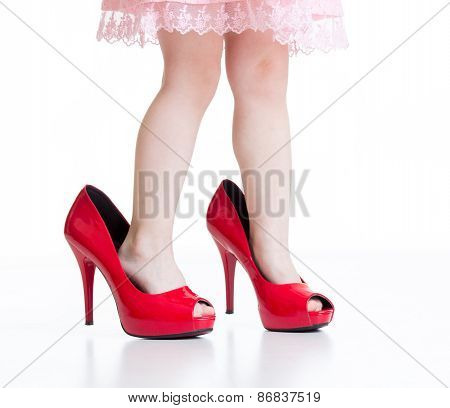 Little child playing with mommy red shoes