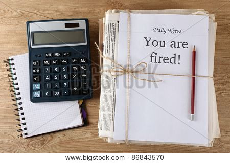 Message You're Fired on stack of newspapers, closeup