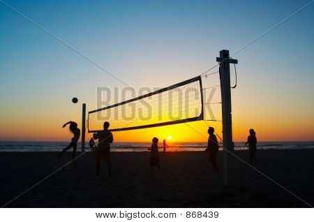 Family playing beach volleyball