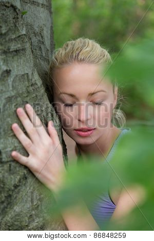 Relaxed young lady embracing a tree receiving life energy from the nature. poster