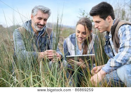 Teacher with students in agronomy looking at vegetation