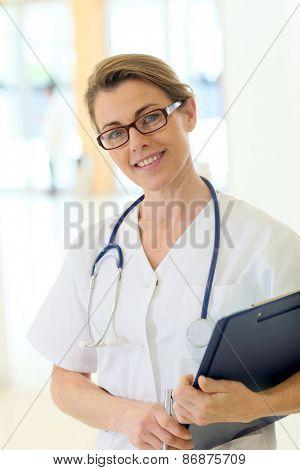 Confident mature nurse standing in hospital corridor