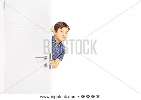 Lovely little boy sneaking a peek behind a door and looking at the camera isolated on white background