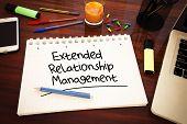 Extended Relationship Management - handwritten text in a notebook on a desk - 3d render illustration. poster