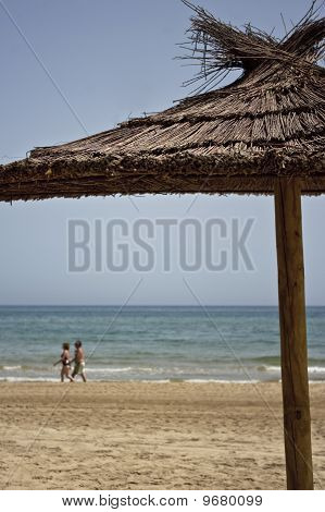 Parasol and couple walking on sandy beach
