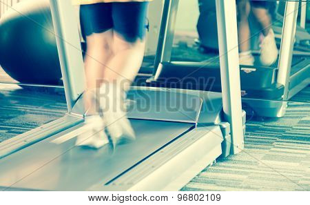 Unknow woman running with treadmill in the gym with motion of speed warm split tone poster