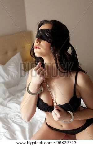 Sensual brunette in handcuffs. Fetish concept
