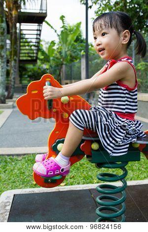 Asian Kid Riding At Park