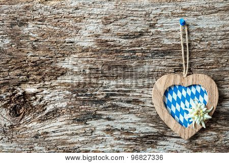 Heart with edelweiss and Bavarian flag on weathered wood background