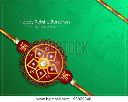 Beautiful creative rakhi on shiny floral design decorated green background for Indian festival, Raksha Bandhan celebration.