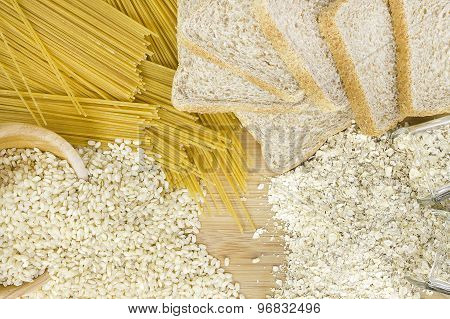Examples of integral food like integral rice in a wooden bowl, oatmeal in small glasses, integral bread and integral pasta. poster
