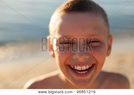 child boy portrait close up, happy laughing braces teeth, sunset backlight