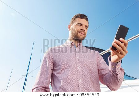 Pleasant man holding mobile phone