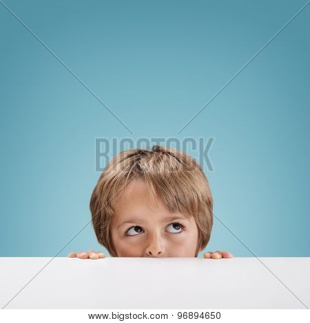 Young boy peeking over a white board looking up at copy space for a message