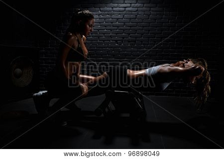 Woman with personal trainer doing fitness in gym poster