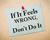 If It Feels Wrong Don't Do It Message written on recycled paper note pinned on cork board. Motivational concept Image poster