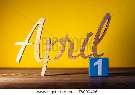 April 1st. Day 1 of month, daily wooden calendar on table and orange background. Spring time concept.