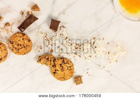 The process of making chocolate chips cookies. Overhead shot of a biscuit with chocolate pieces, flour, cane sugar, and egg yolk, with a place for text