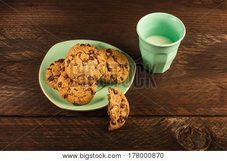 A plate of chocolate chips cookies on a dark wooden background, with a glass of milk and copy space