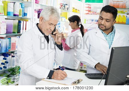Chemist Taking Order On Phone While Colleagues Working In Pharma