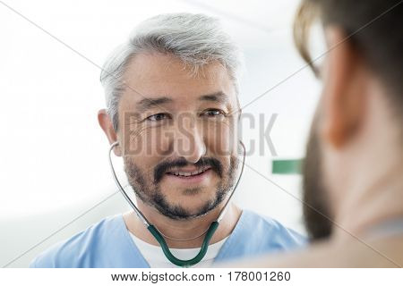 Smiling Doctor Wearing Stethoscope While Looking At Patient