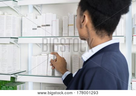 Businesswoman Selecting Medicine In Pharmacy