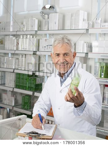 Male Pharmacist Holding Product While Writing On Clipboard