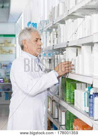 Pharmacist Arranging Medicines On Shelf
