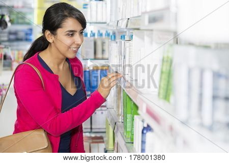 Woman Looking At Cosmetics On Shelf In Pharmacy