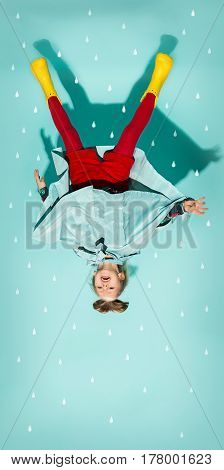 Little girl posing in fashion style wearing autumn clothing on blue background. Rubber yellow boots. upside down view