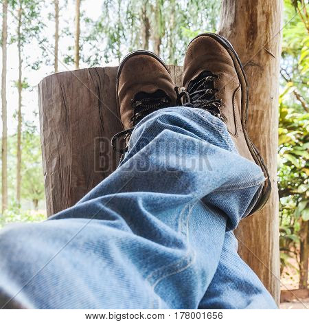 Resting with legs up crossed wearing boots leaning on a wooden stump. Rural scene.