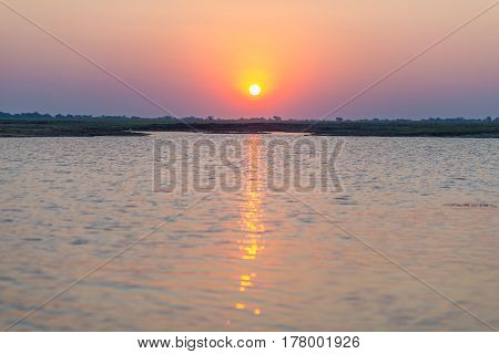 Chobe River In Backlight At Sunset. Scenic Colorful Sunlight At The Horizon. Wildlife Safari And Boa