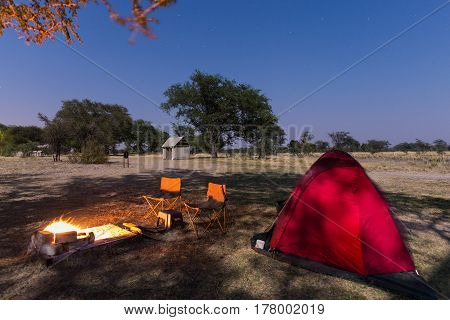 Camping site with starry sky by night. Adventure in National Park Africa. Burning camp fire and tent in the background.
