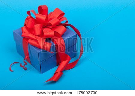 Blue gift box with red ribbon and bow on blue background