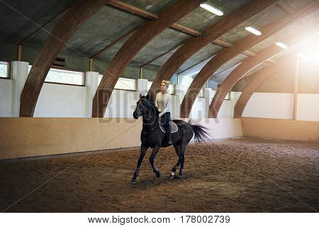 Short-haired Woman Riding A Beautiful Black Horse
