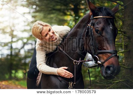 Woman Patting Her Horse On The Neck
