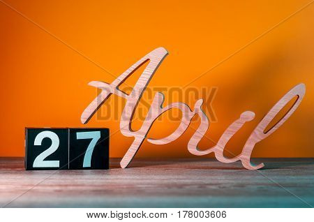 April 27th. Day 27 of month, daily wooden calendar on table with orange background. Spring time concept.