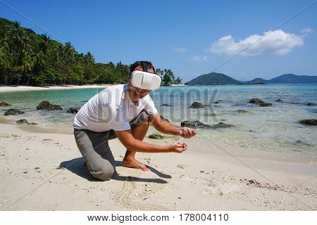Man in Virtual Reality Glasses Touching Sand on the Beach in Thailand