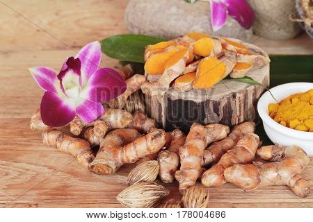 Turmeric root with turmeric powder on wood background