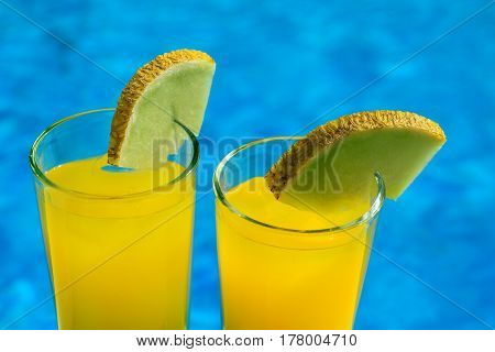 Glasses with yellow cocktail in front of a swimming pool with clear water. Macro photo of cocktails.