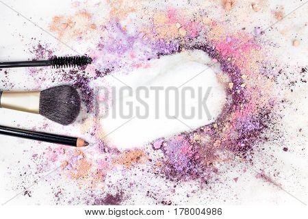 Makeup brush, pencil, and mascara applicator on white marble background, with traces of powder forming a frame. Horizontal template for a makeup artist's business card or flyer design, with copy space