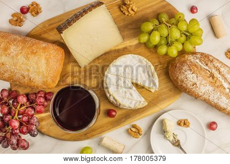 An overhead photo of a glass of red wine with cheese, white and rye bread, purple and green grapes, and walnuts, at a wine pairing