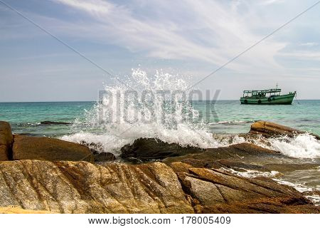 Big waves crashing on ruins rocks at coast with blue sky and boat background