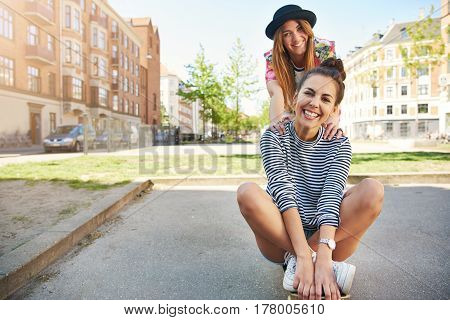 Cute Young Woman Sitting On A Skateboard