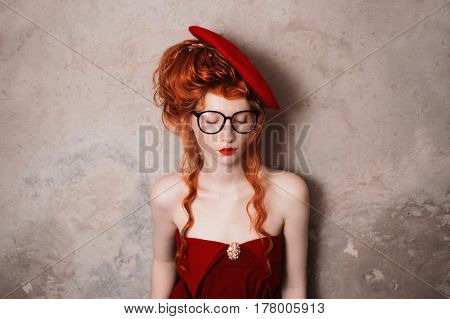 Red-haired woman. French woman courtesan. Beautiful woman with red hair and pale skin. A woman in a red retro dress. Model posing in studio. Insidious wicked witch woman. Redhead woman. Woman in studio. Gothic retro woman