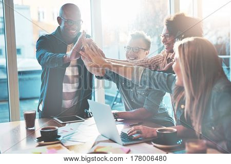 High Fiving Coworkers At Table In Office