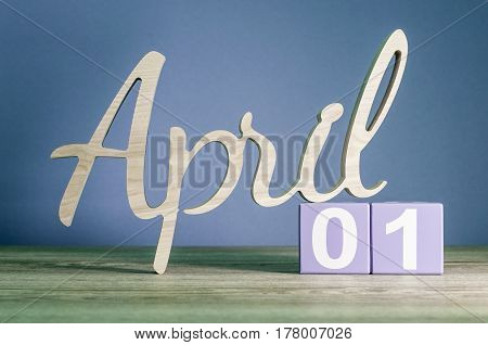 April 1st. Day 1 of month, daily calendar on wooden table with purple or violet background. Spring time theme.