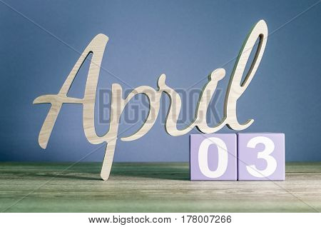 April 3rd. Day 3 of month, daily calendar on wooden table with purple or violet background. Spring time theme.